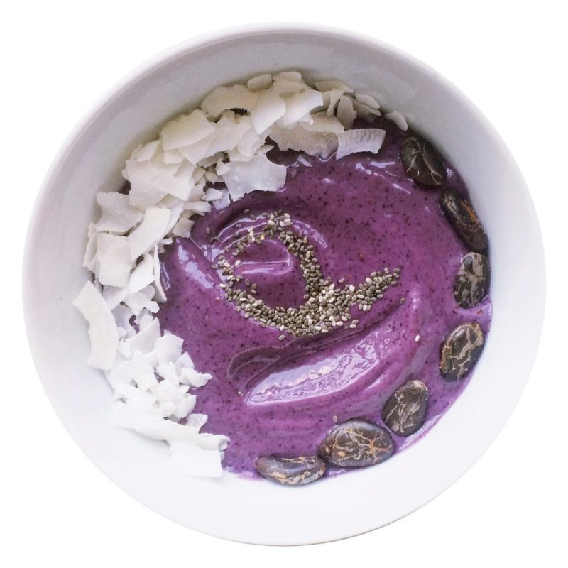 Purple smoothie bowl with cacao beans