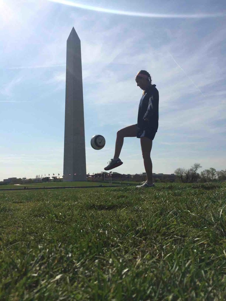 Claire haft juggling soccer ball in front of the Washington monument